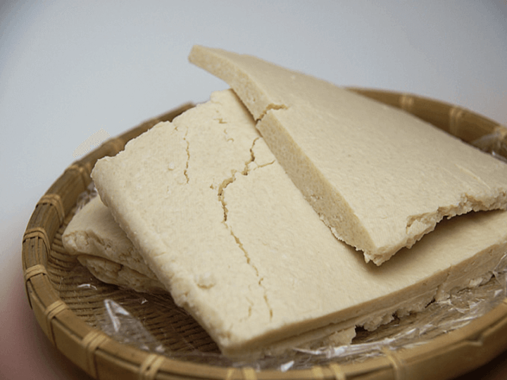 Bricks of sake-kasu paste is pictured, layering on top of each other.