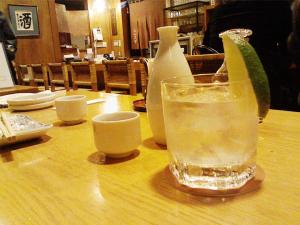 A glass of sake on the rocks with some Tokkuri carafes at an Izakaya setting.