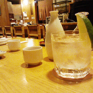 A glass of sake on the rocks with some Tokkuri carafes at an Izakaya setting.