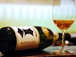 Bottle of Kenbishi sake with a wine glass containing sake.