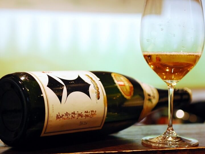Bottle of Kenbishi sake with a wine glass containing sake.