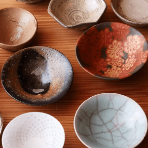 "Variety of colorful ""ochoko"" sipping cups on a wooden surface."