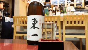 """bottle of """"Azumaichi"""" sake served into a glass and """"masu"""" box"""