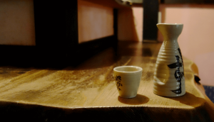 """""""tokkuri"""" carafe and """"ochoko"""" cup holding sake"""