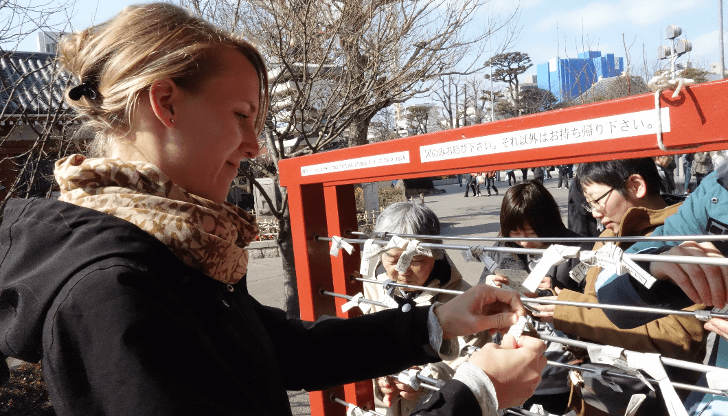 someone tying their omikuji to a rack