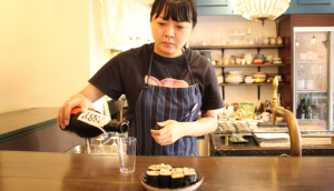 Marie Chiba is pouring sake into a glass